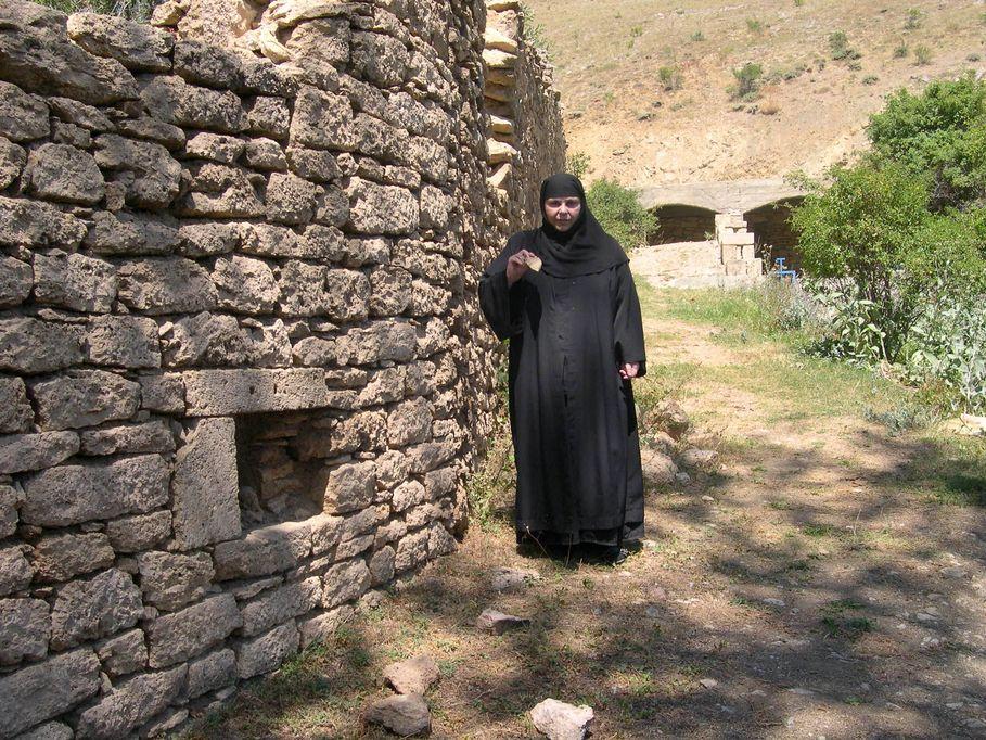 Η Ηγουμένη Μαριάμ στην εξωτερική περίφραξη των κελίων της Μονής, όπου κρατάει τεμάχιο πέτρας το οποίο μετέφερε πίσω στην Ελλάδα και φυλάσσεται στην Ιερά Μονή Αγίας Παρασκευής.